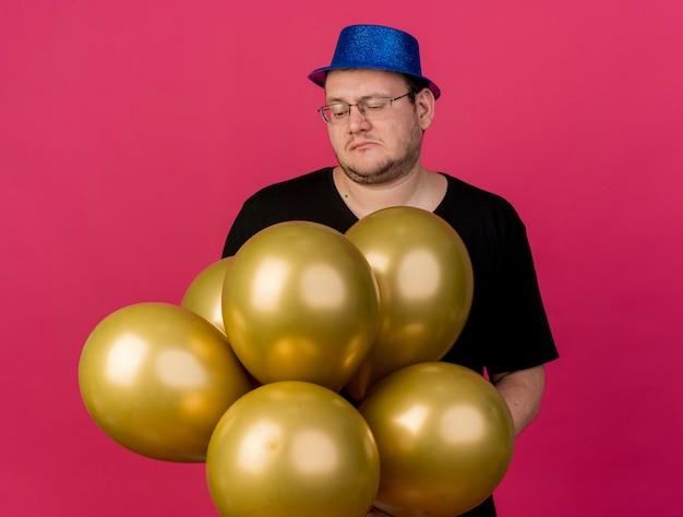 Teleurgestelde volwassen slavische man met een optische bril met een blauwe feestmuts houdt vast en kijkt naar heliumballonnen