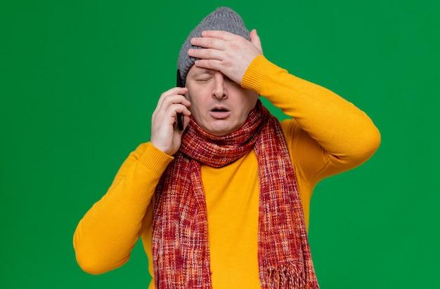 Teleurgestelde volwassen slavische man met wintermuts en sjaal om zijn nek die aan de telefoon praat en hand op zijn voorhoofd legt