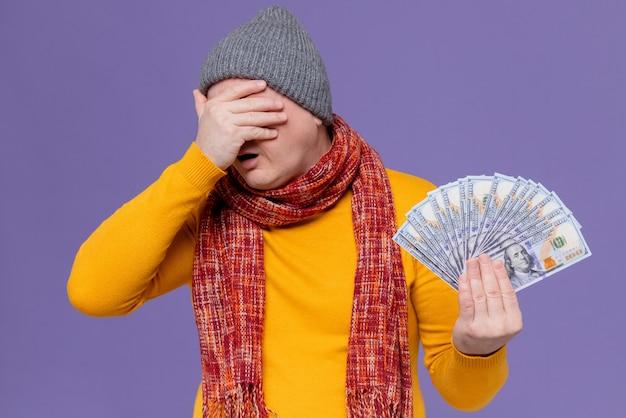 Teleurgestelde volwassen slavische man met wintermuts en sjaal om zijn nek die geld vasthoudt en hand op zijn voorhoofd legt