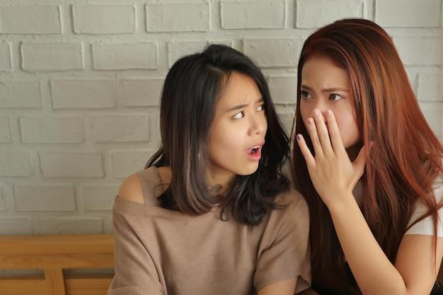 Teleurgestelde vrouw die roddelt, fluistert, luistert naar geruchten of geruchten