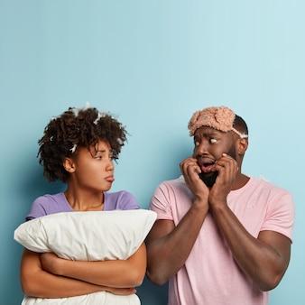 Teleurgestelde zwarte man voelt zich nerveus, sombere droevige vrouw met donkere huid houdt kussen vast, drukt negatieve emoties uit, slaapt slecht, enge dromen, draagt casual t-shirts, poseert over blauwe muur met vrije ruimte