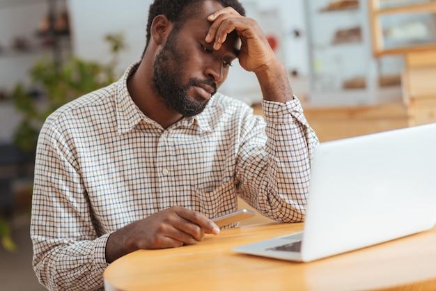 Teleurstellend bericht. boos jonge man zit in het café, houdt zijn telefoon vast en kijkt verdrietig, nadat hij een sms heeft gelezen
