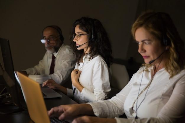 Telewerkers in headsets in een donker kantoor