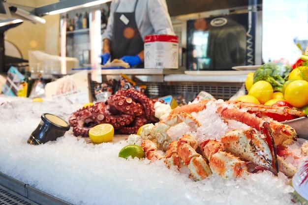 Teller met bevroren zeevruchten in ijs in de winkel octopus en krab