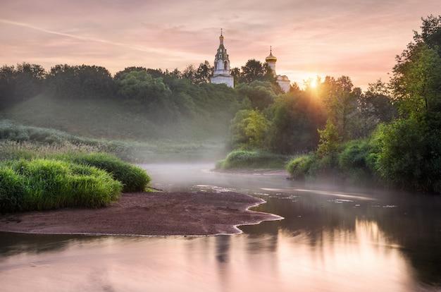 Tempel op de hoge oever van de rivier de istra op een vroege mistige ochtend