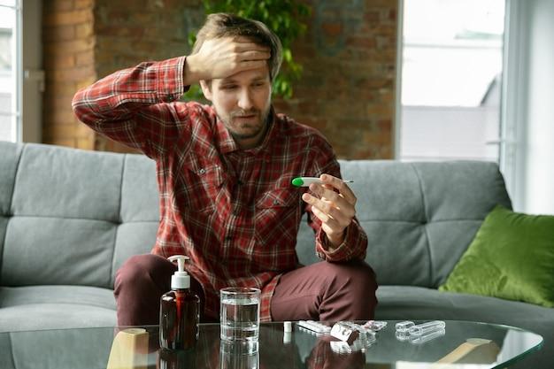 Temperatuur opnemen. blanke man blijft thuis tijdens quarantaine vanwege coronavirus, verspreiding van covid-19. proberen tijd nuttig en leuk door te brengen. concept van gezondheidszorg en geneeskunde, isolatie.