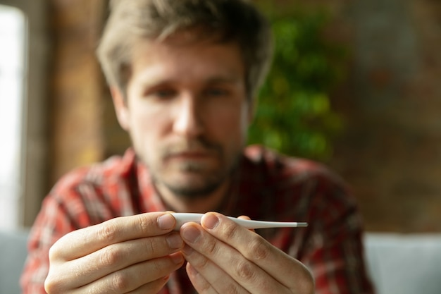 Temperatuur opnemen. blanke man blijft thuis tijdens quarantaine vanwege coronavirus, verspreiding van covid-19
