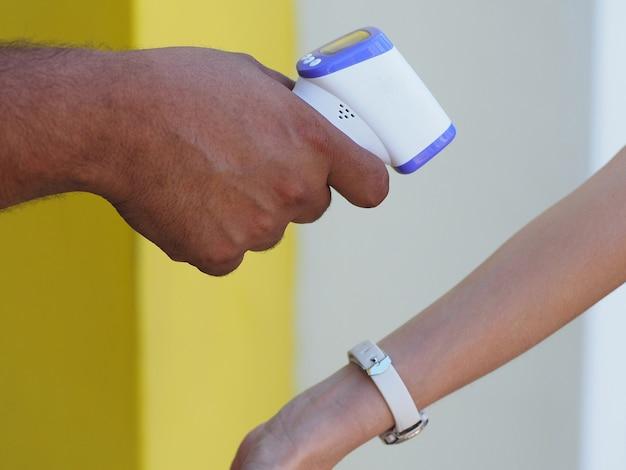 Temperatuurmeting door elektronische infraroodthermometer van een vrouwenhand bij de ingang van een supermarkt. coronapandemie. levensstijl.
