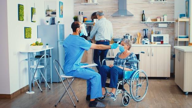 Temperatuurmeting met behulp van infraroodthermometer op gehandicapte oudere vrouw in rolstoel tijdens huisbezoek in coronaviruspandemie. maatschappelijk werker met vizier en masker die covid-19-preventie helpt