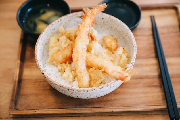 Tempura donburi, gebakken garnalen tempura op rijst japans eten op houten tafel Premium Foto