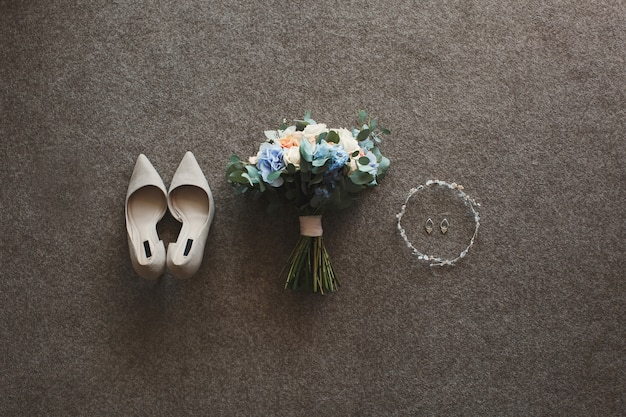 Tender beige trouwschoenen en oorbellen en een bruidsboeket