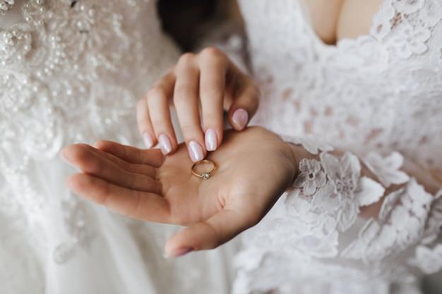 Tender gouden verlovingsring met diamant op de hand van de vrouw met manicure en decollete trouwjurk