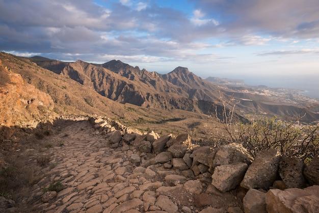 Tenerife berglandschap. trekking pad. de kustlijn van adeje en van las-amerika op de achtergrond.