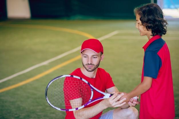 Tennis. coach in een rode pet en een jongen met een tennisracket in een sportschool