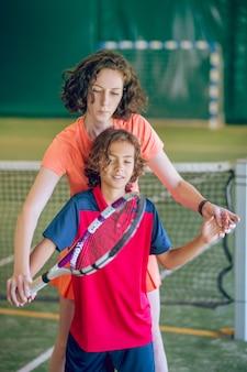 Tennis coaching. jonge schattige vrouwelijke coach die een jongen leert om een tennisracket vast te houden