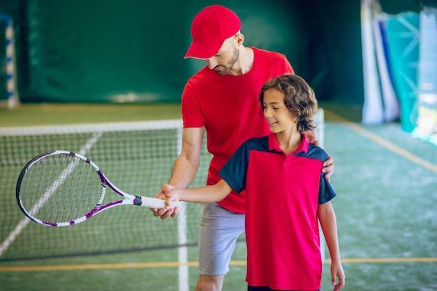 Tennis. mannelijke tenniscoach die een jongen toont hoe hij het racket moet vasthouden