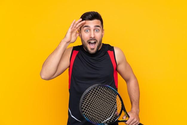 Tennis speler man over geïsoleerde gele muur met verrassing en geschokt gelaatsuitdrukking