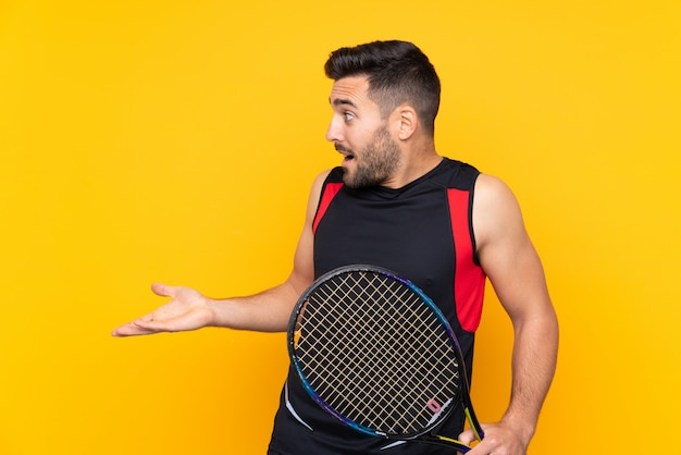 Tennis speler man over geïsoleerde gele muur met verrassing gelaatsuitdrukking