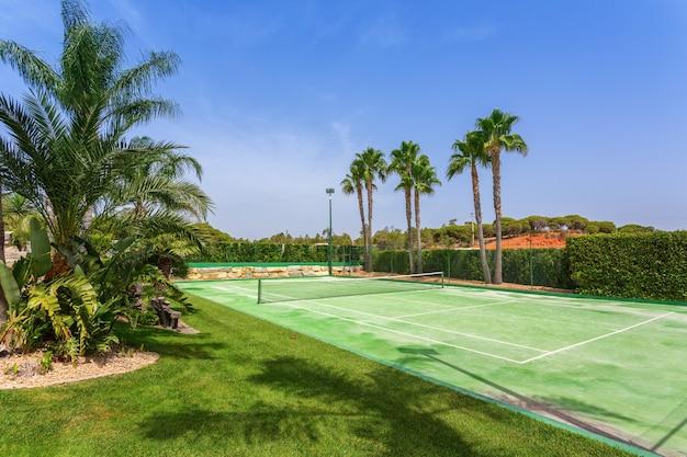 Tennisbaan in de tuin met palmbomen in portugal.