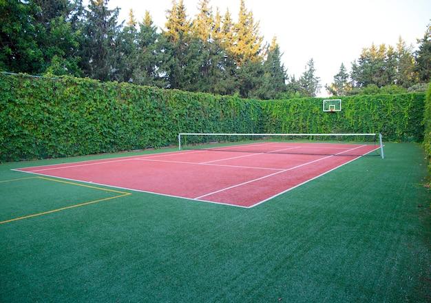 Tennisbaan met harde ondergrond en groene omheining
