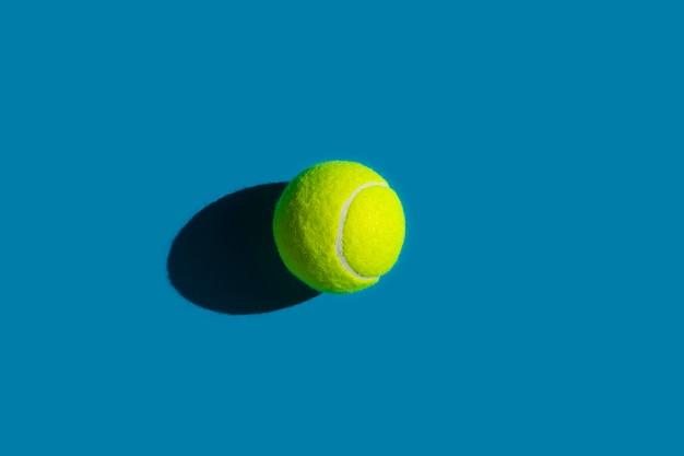 Tennisbal met sterke schaduw op blauw