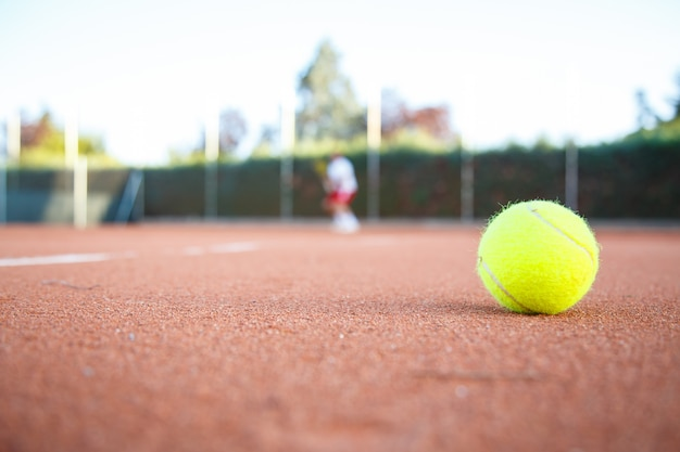 Tennisbal op de vloer van een tennisbaan in een wedstrijd in de schaduw.