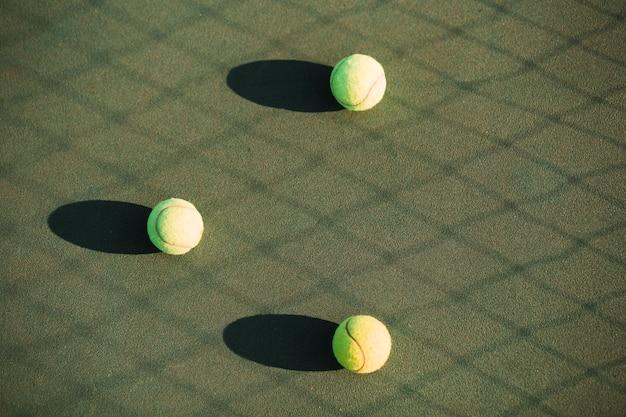 Tennisballen op het tennisveld en netto schaduw