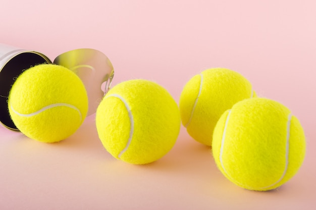 Tennisballen zijn net geopend en klaar om te spelen op een roze achtergrond. tennis competitie concept