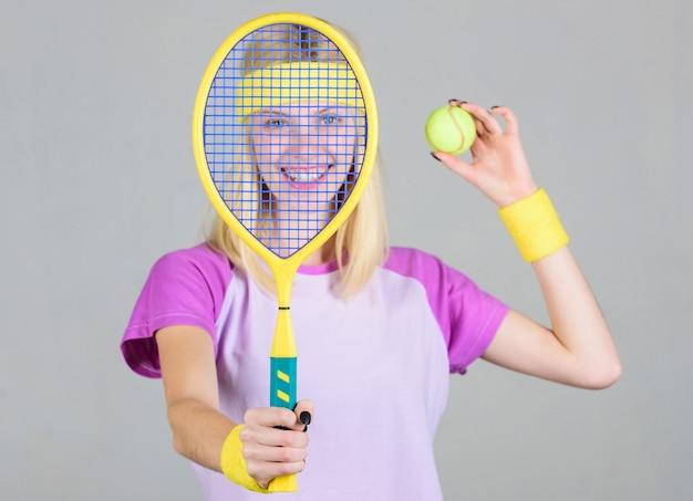 Tennisclub-concept. tennissport en amusement. actieve vrije tijd en hobby. meisje fit slanke blonde tennissen. sporten voor het behoud van de gezondheid. actieve levensstijl. vrouw houdt tennisracket in de hand.