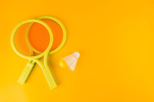 Tennisknuppels met shuttle en bal op gele achtergrond