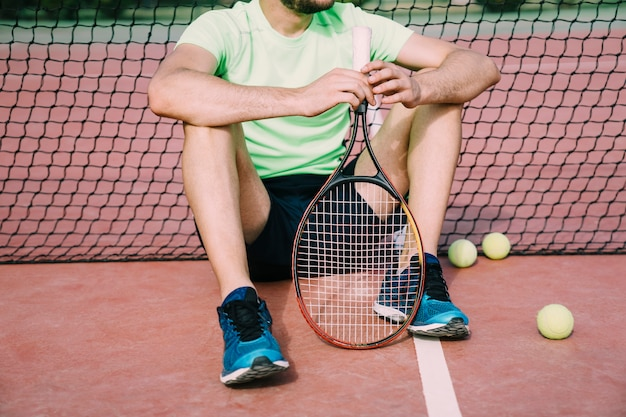 Tennislaag leunend tegen netto