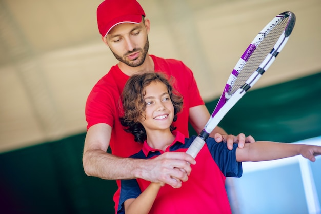 Tennisles. mannelijke tenniscoach in rode kleren teacjing een jongen om het racket vast te houden