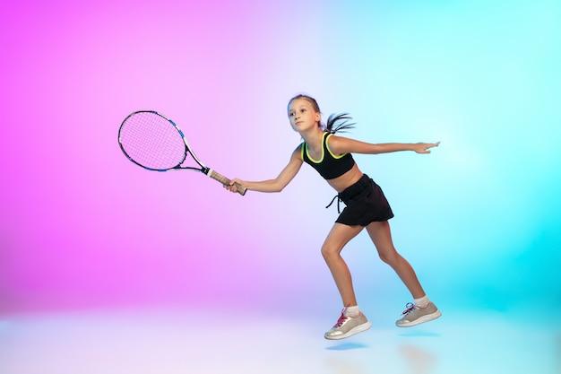 Tennismeisje in zwarte sportkleding geïsoleerd op gradiëntmuur in neonlicht