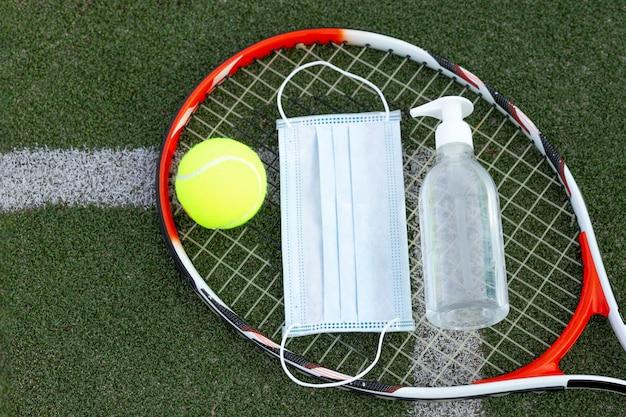 Tennisracket, bal, medicijnmasker en ontsmettingsmiddel op groen gras kort. bovenaanzicht.
