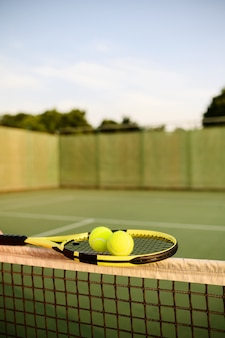 Tennisracket en ballen op het net, niemand, buitenbaan