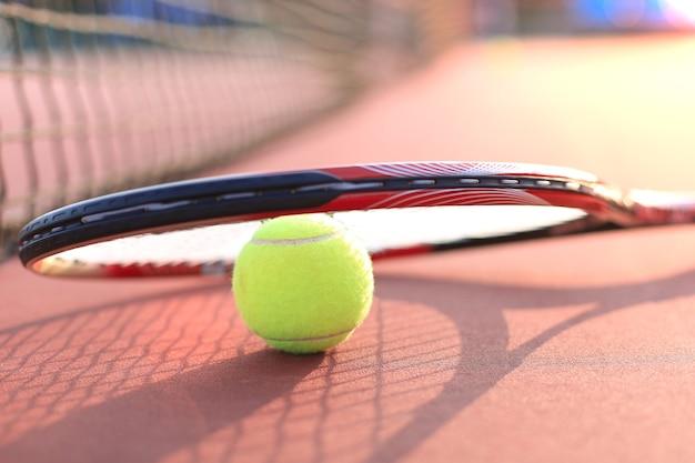 Tennisracket en de bal op de tennisbaan.
