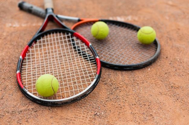 Tennisrackets met ballen op het veld