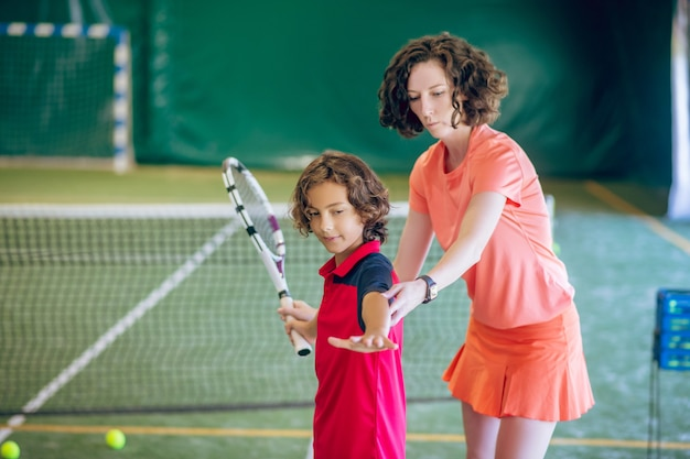 Tennissen. vrouw in lichte kleren die een jongen leert hoe hij een tennisbal moet raken