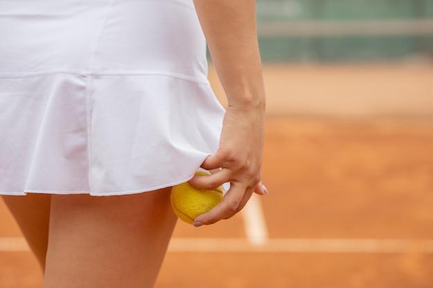 Tennisser in witte sportkleding voorbereiding om tennisbal te dienen, training voor wedstrijd.