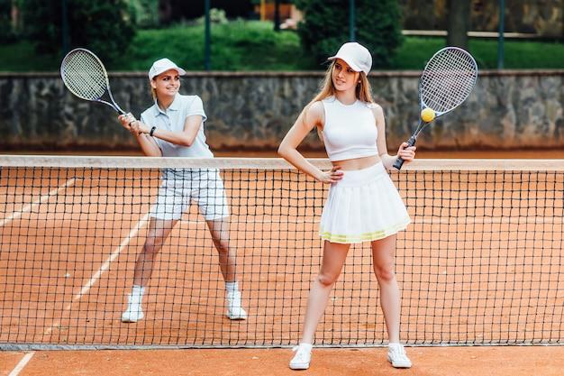 Tennissers spelen een wedstrijd op het veld op een zonnige dag met rackets.