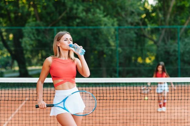 Tennisspeelster met handdoek op haar schouders drinkwater na wedstrijd