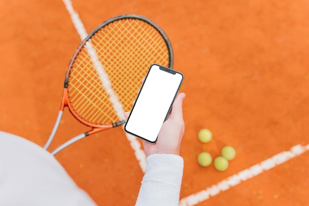 Tennisspeler die een smartphone houdt