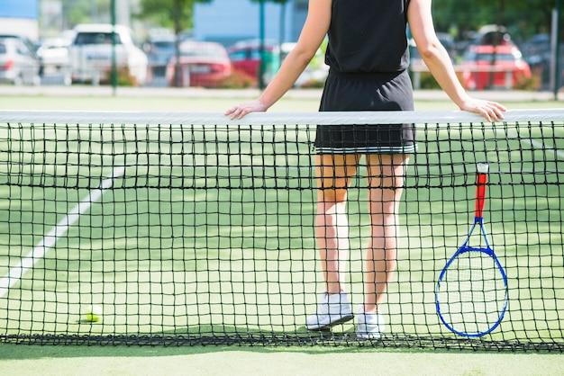 Tennisspeler met racket die zich achter het net bevindt