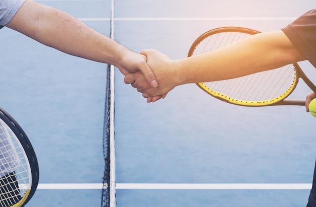 Tennisspelers die hand schudden vóór gelijke op tennisbaan