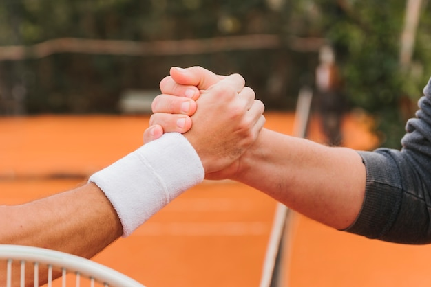 Tennisspelers die handen houden