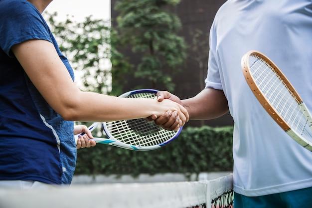 Tennisspelers die handen schudden na een goede match