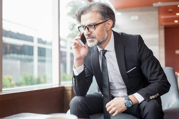 Tensed business man praten over smartphone in de lobby