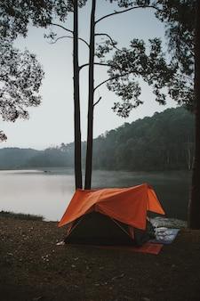 Tent met sinaasappel aan de waterkant.