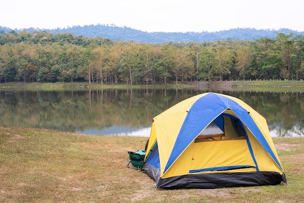 Tent op groen gras naast meer.