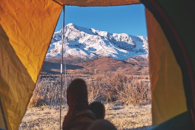 Tent uitkijk op een kamp in de bergen. voeten wandelaar genieten van uitzicht vanaf tent camping ingang buiten ontspannen.